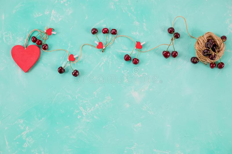 Love composition, flat lay for Valentines day. Red heart and sweet fresh cherries isolated on green backgrouns. Copy. Love letter and gift box on Valentines day royalty free stock photography