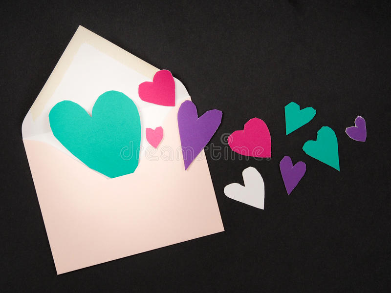 Love letter. Real cut out of paper hearts coming out of an envelope for your romantic copy royalty free stock image