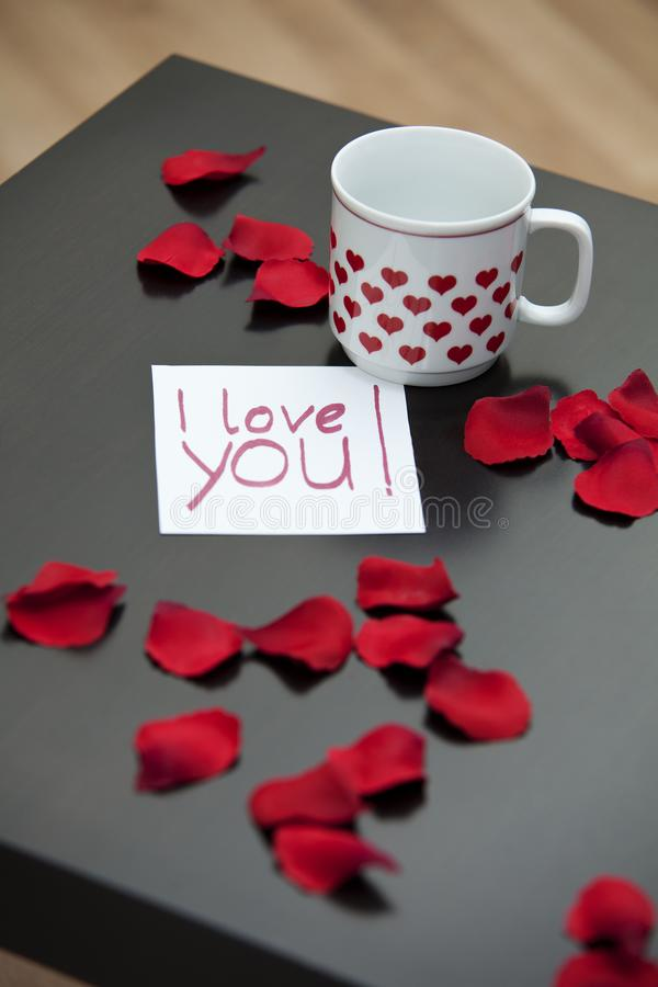 Love letter, rose petals and a cup on a dark coffee table. royalty free stock images