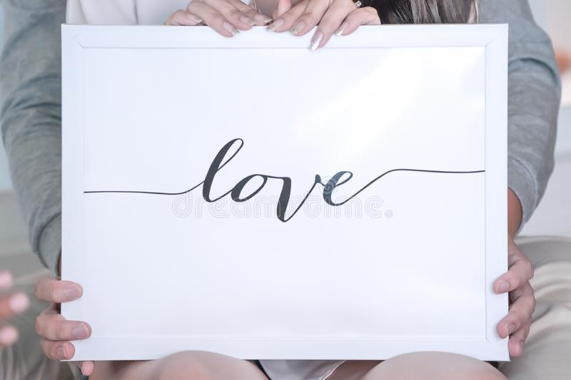 LOVE letter in the white frame and background, Hold by bride and groom behind stock image