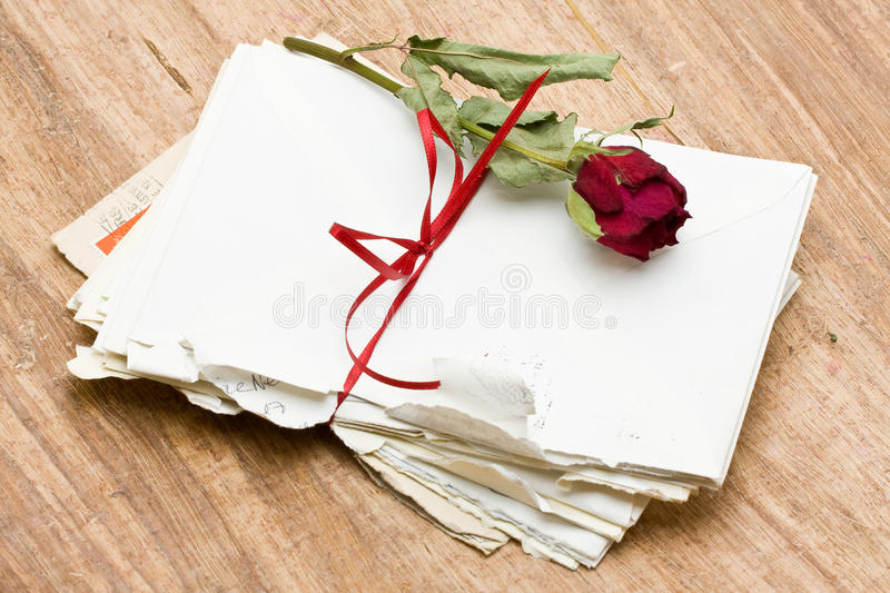 Love letters. Vintage love letters with red rose over wood background royalty free stock photo