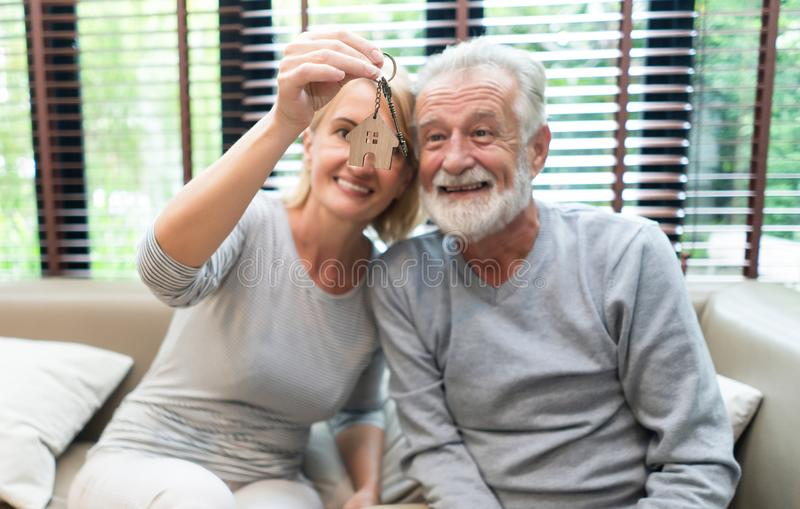 Love lives forever!  Happy Senior Couple are spending time together while sitting on sofa with keys in hands. Retirement couple royalty free stock images