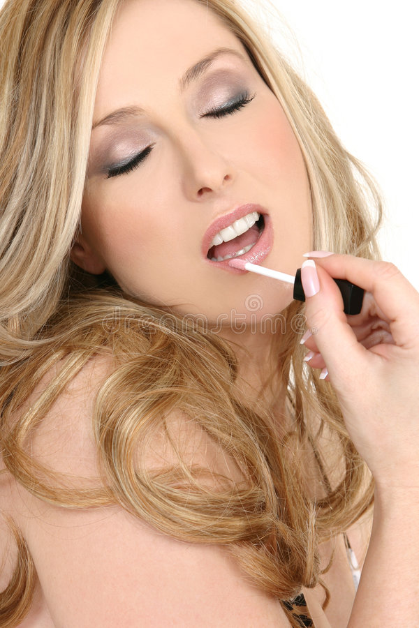 Love Makeup and Cosmetics. Female with beautiful makeup applies a slick of pink lip gloss to lips stock photography