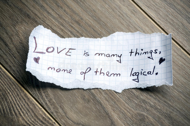 Love is many things. None of them logical (Quote by William Goldman) - Hand writing text on a piece of paper on wood background stock photos