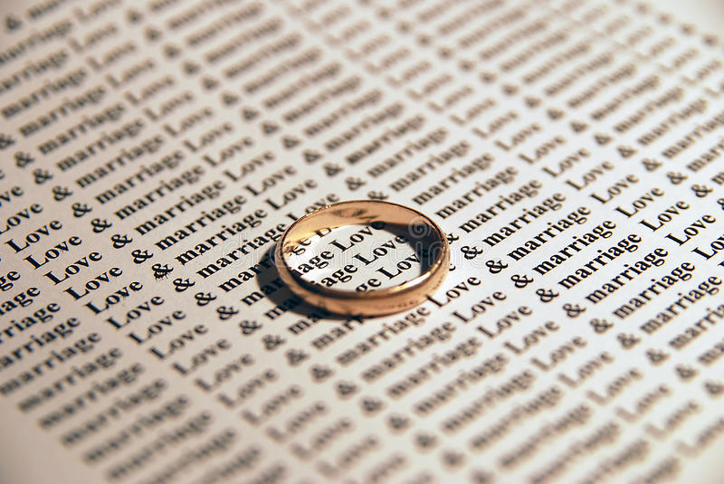 Love & Marriage. A wedding ring on top of a Love & Marriage text stock photos