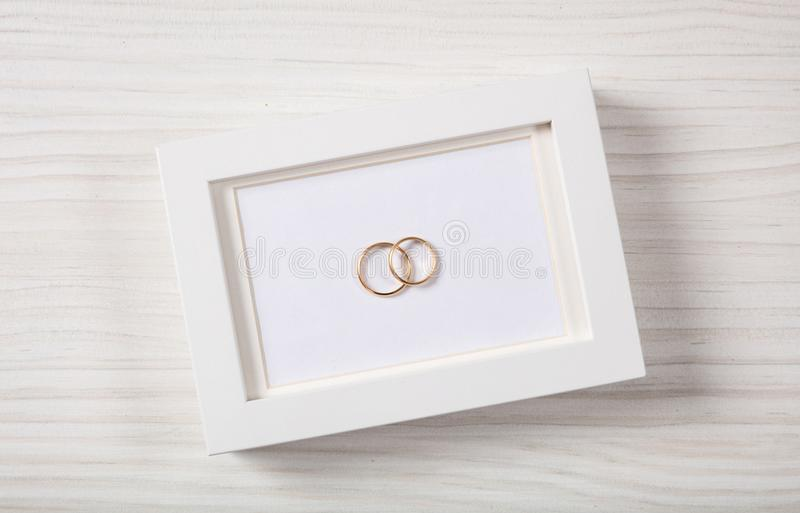 Golden wedding rings on a blank white photo frame, top view, on a white wooden background. stock images
