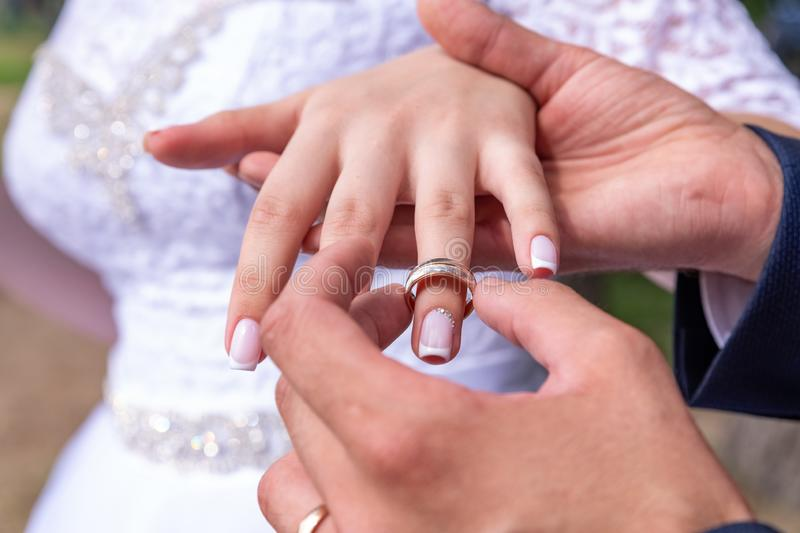 Love and marriage. Wedding ceremony. Close up of groom putting golden ring on the bride& x27;s finger stock image