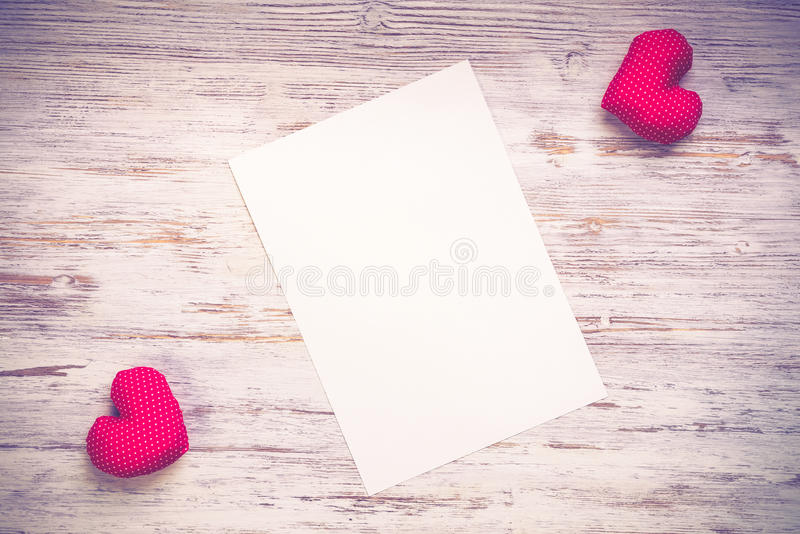 Love message or invitation. Hearts and sheet of blank paper on wooden table royalty free stock images