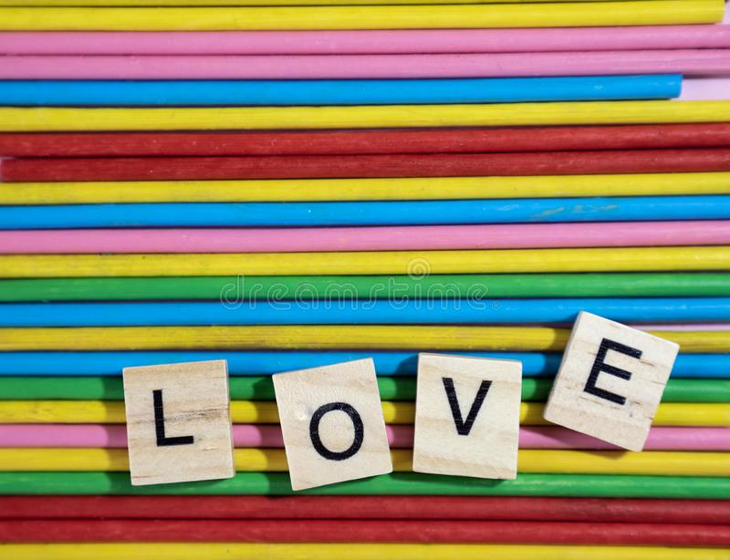 Love message written in wooden blocks placed on colourful wood s stock images