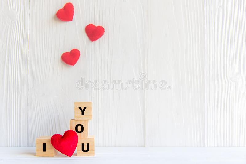 Love message written in wooden blocks with red heart, white wood background. stock photo