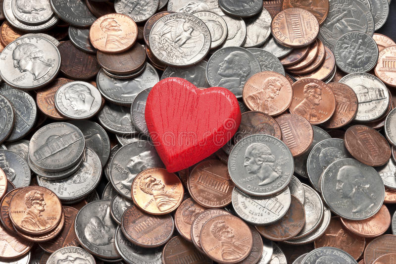 Love Money Management Marriage Divorce. A conceptual image about marriage, love and finances with a red heart on American coins background stock images
