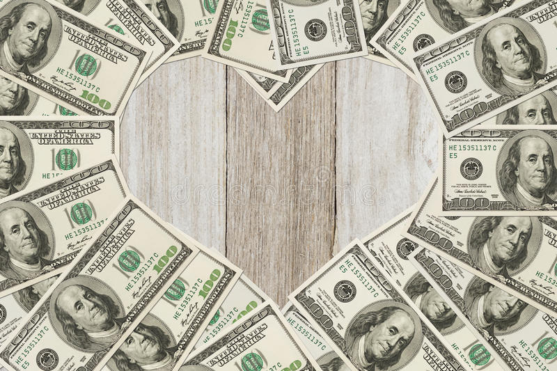 The love of money. One hundred dollar bill in the shape of a heart with a weathered wood heart with copy space for your message stock photos