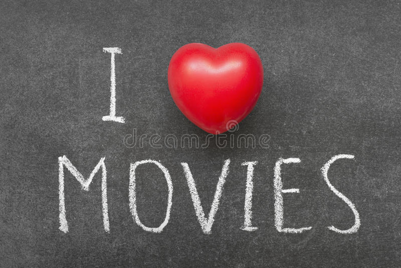 Love movies. I love MOVIES phrase handwritten on chalkboard with heart symbol instead of O royalty free stock images