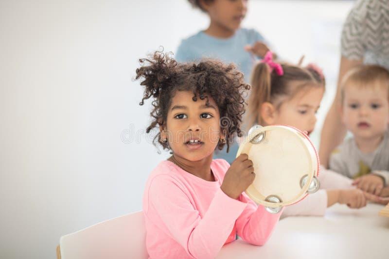 She love music. Children in preschool stock photography