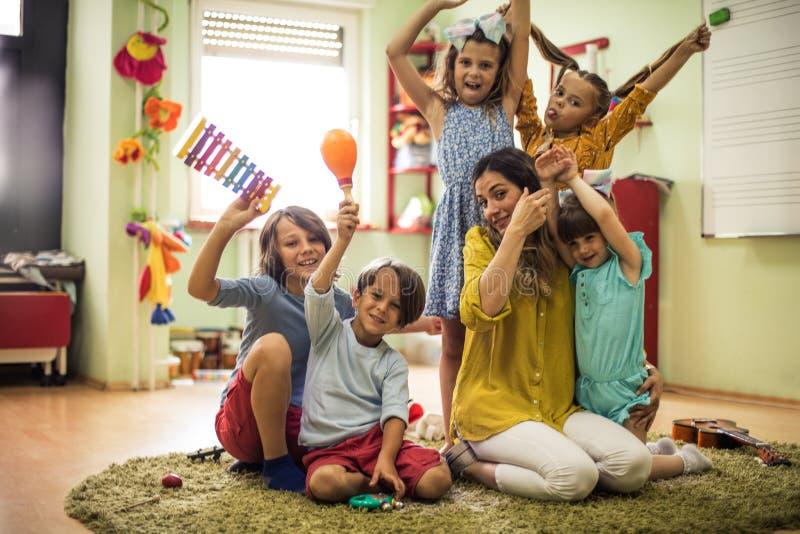 We love music. Children with teacher in preschool royalty free stock photo