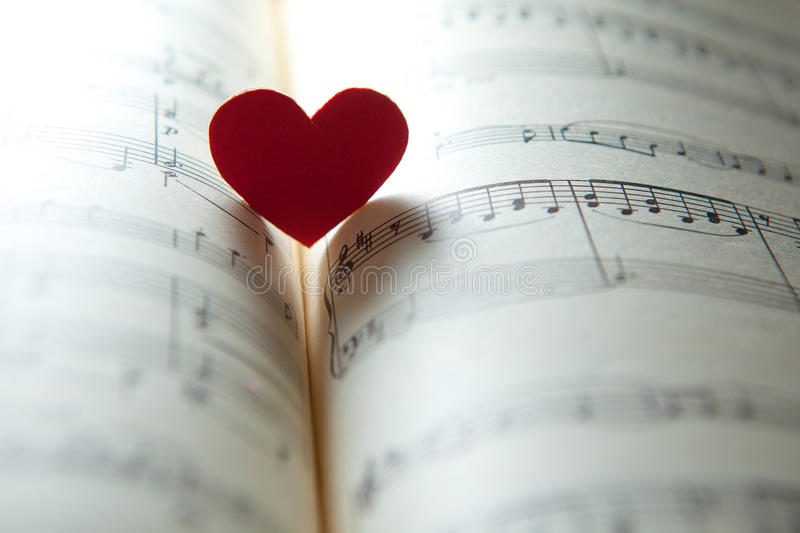 Love for music. Heart shape on a music note book. shallow DOF
