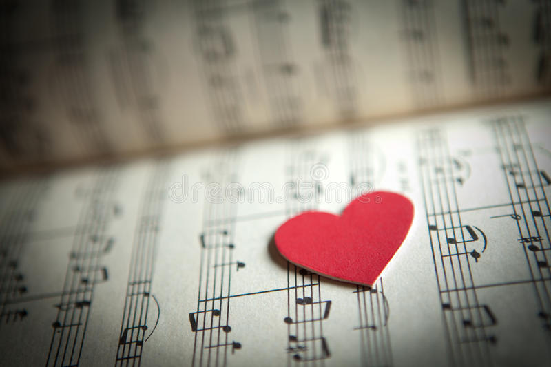 Love for music. Heart shape on a music note book. shallow DOF stock photography