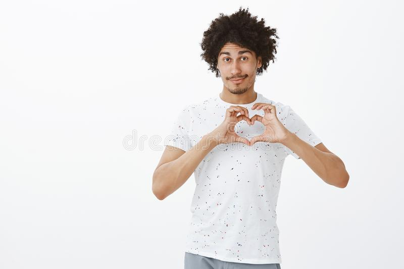 Love my friends. Cute friendly-looking relaxed hispanic male with tanned skin and afro hairstyle showing heart sign over royalty free stock photography