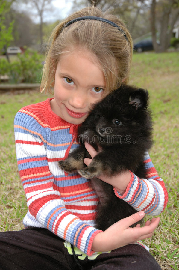Love my Puppy. Little girl hugs her new pomeranian puppy stock photo