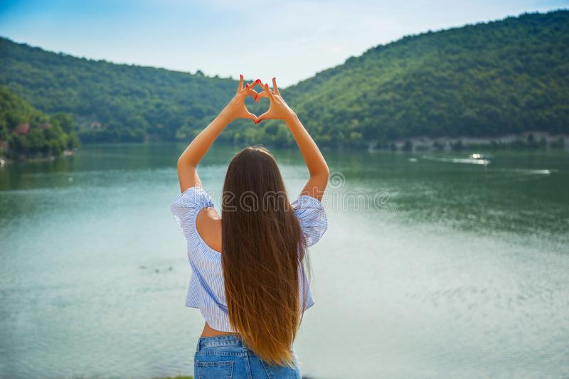 Love nature, traveling, vacation concept. Beautiful young brunette girl holding hands in heart shape framing stock photos