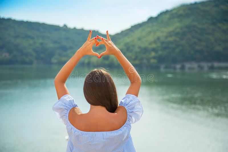 Love nature, traveling, vacation concept. Beautiful young brunette girl holding hands in heart shape framing stock image