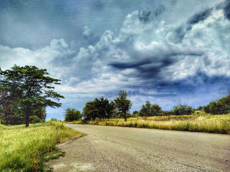 Love nature. Trees, road, you can do it. Road. Sky. Clouds. Look up. Love is in the air.  Road in the villege stock image