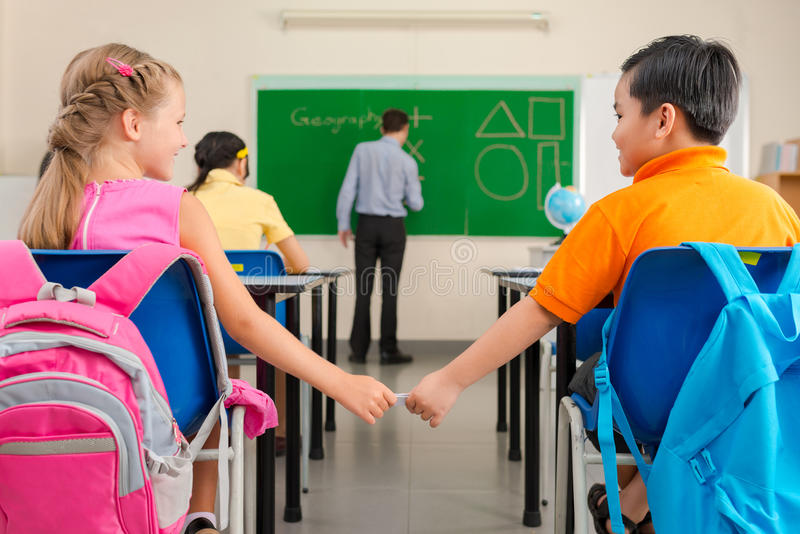 Love note. Schoolboy passing a love note or cheat sheet to his classmate in classroom, rear view royalty free stock image