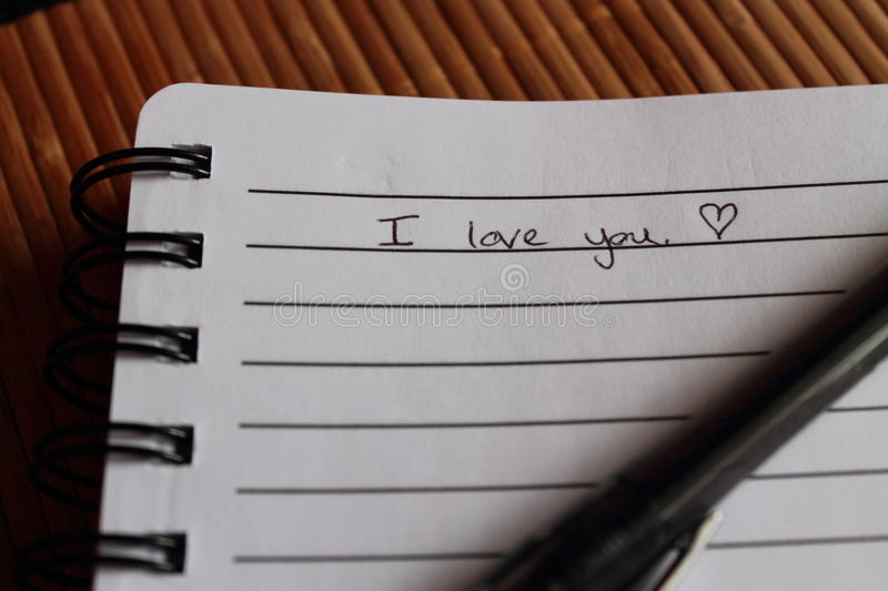 Love note. A simple love note, declaring love. a pen lies across the notebook stock photo