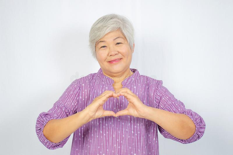 Happy senior woman showing hand heart gesture and smiling, take care of the health, or being in love stock photo