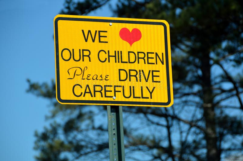 Drive carefully sign. Yellow roadside style sign with text 'we love our children please drive carefully', blue sky and fir tree in background royalty free stock photo