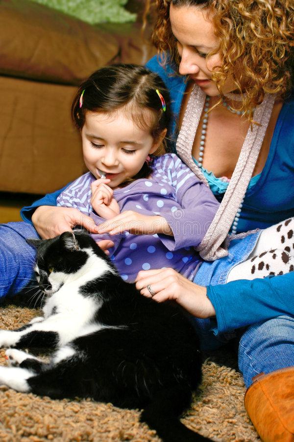 We love our kitty cat. Young girl stroking the family pet cat while sitting with her mother, in a home environment royalty free stock photo