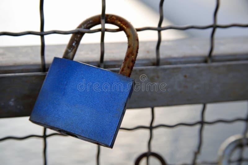 Love padlock chained to bridge. Blue love padlock chained to bridge stock photography