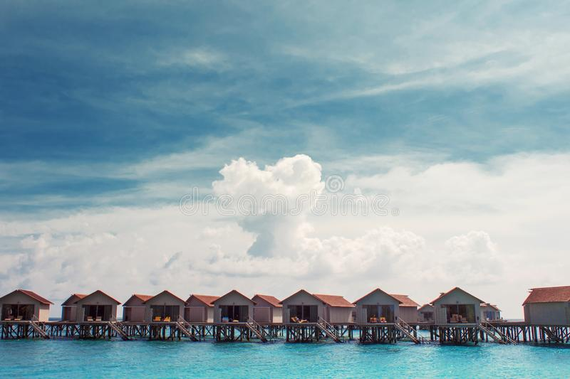 Love on Paradise island, concept. Bungalow on stilts in the water, amazing tropical nature. Maldives resort royalty free stock photos