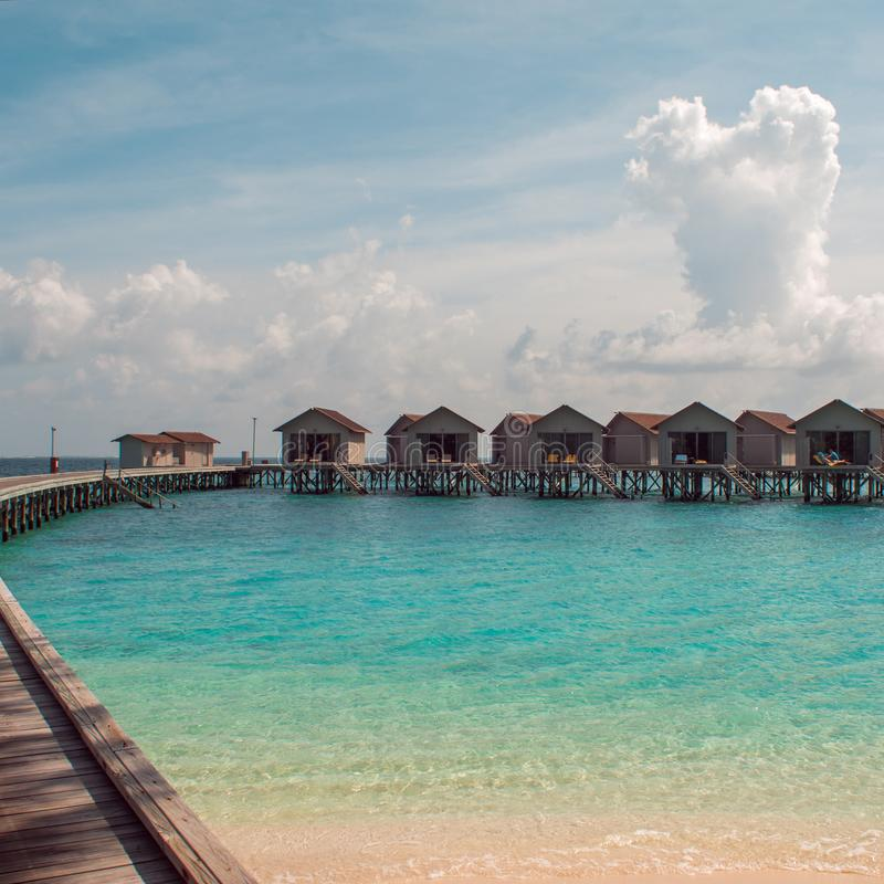 Love on Paradise island, concept. Bungalow on stilts in the water, amazing tropical nature. Maldives resort. stock photography