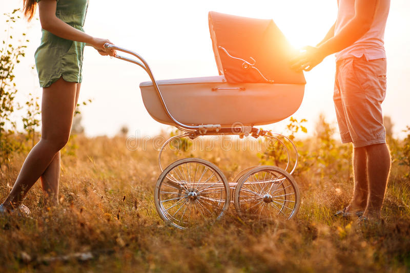 love, parenthood, family, season and people concept - smiling couple with baby pram in autumn park. on sunset royalty free stock photo