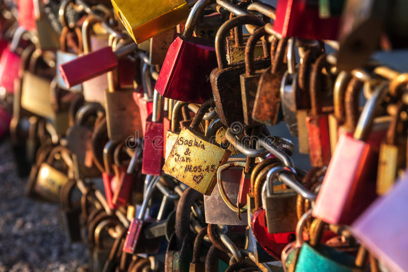 Love pedlocks in red and gold locked at a bridge at a tourists p royalty free stock image