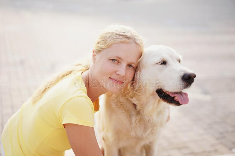 Love for pets - a young blonde woman resting with her dog on the street stock image