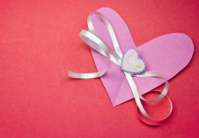 Love on a pink Valentine. With a pink ribbon on a red background with space for a message stock photos