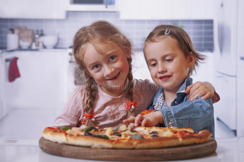 We love pizza! Cute little girls best friends eating pizza. royalty free stock photo