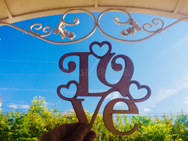 Love plate on the background of a clear sky under a forged roof stock image