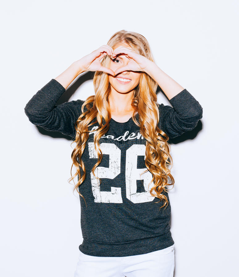 Love. Portrait smiling happy young woman with long blond hair, making heart sign, symbol with hands white wall background. Positiv royalty free stock photos