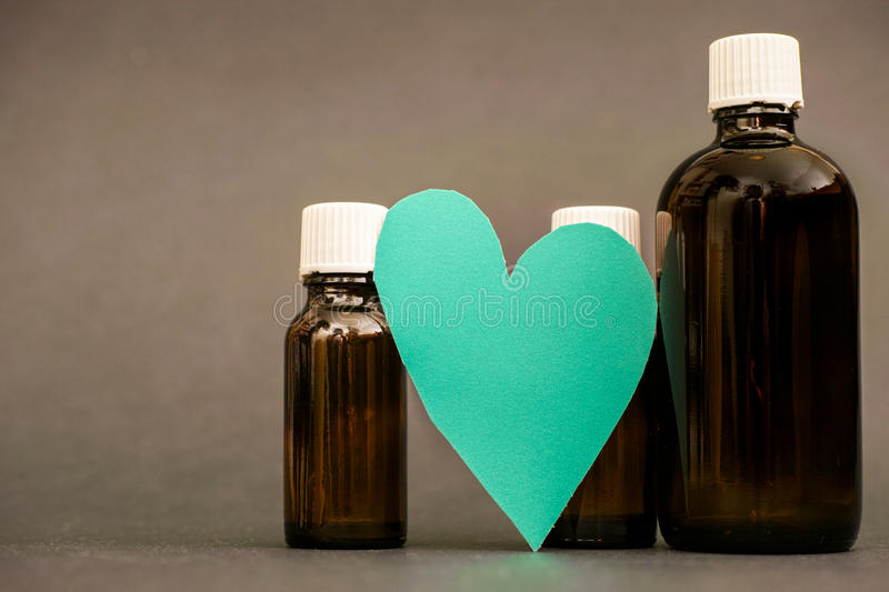 Love potion. Real cut out of paper heart leaning on medical flasks for your romantic or healthcare copy royalty free stock images