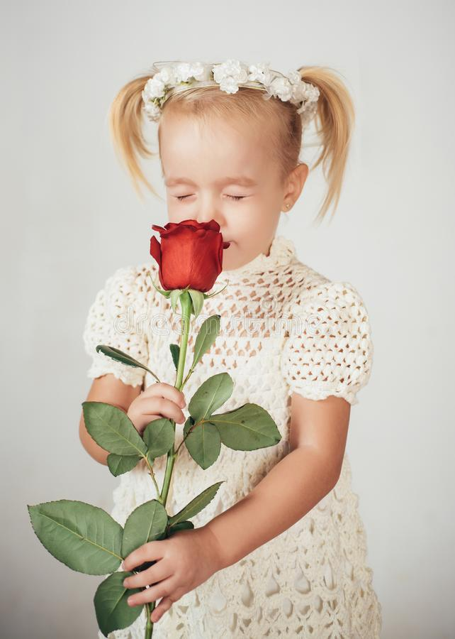 Love present. childrens day. small kid with red rose. happy childhood. valentines day. romantic date. little girl in. Love present. childrens day. smalid with royalty free stock photography