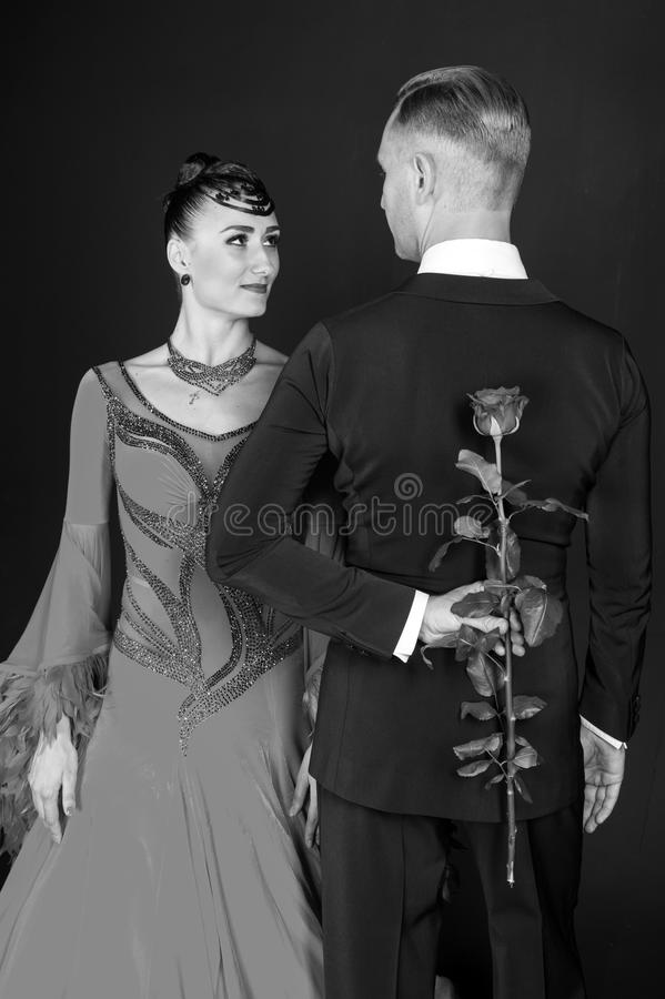 Love proposal and date concept. Couple of ballroom dancers in love. Sensual woman and man hide rose flower. Woman in dress and mac. Love proposal and date stock photo