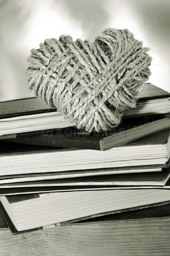 Love for reading. A pile of books and a heart-shaped coil of rope symbolizing love for reading habit stock images