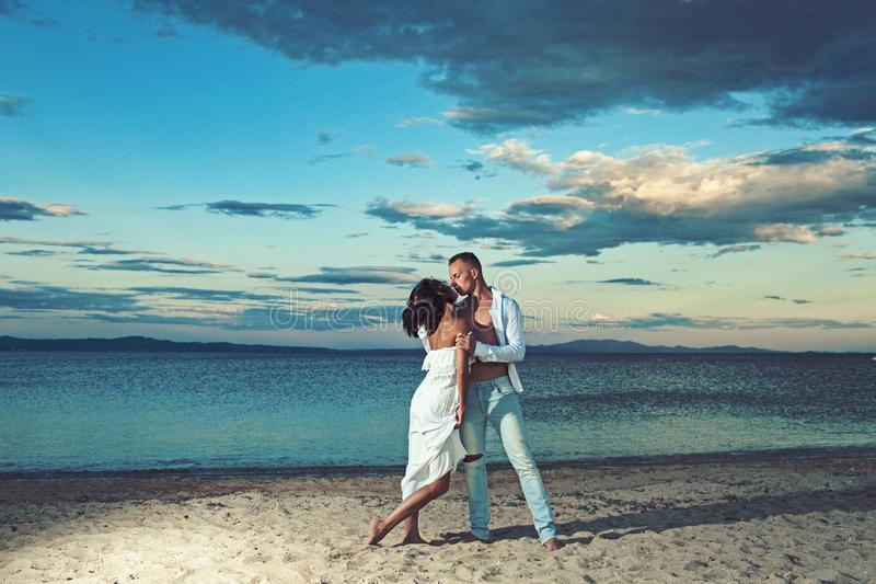 Love relations of kissing couple enjoying summer day together. Family and valentines day. Couple in love relax on beach royalty free stock photo
