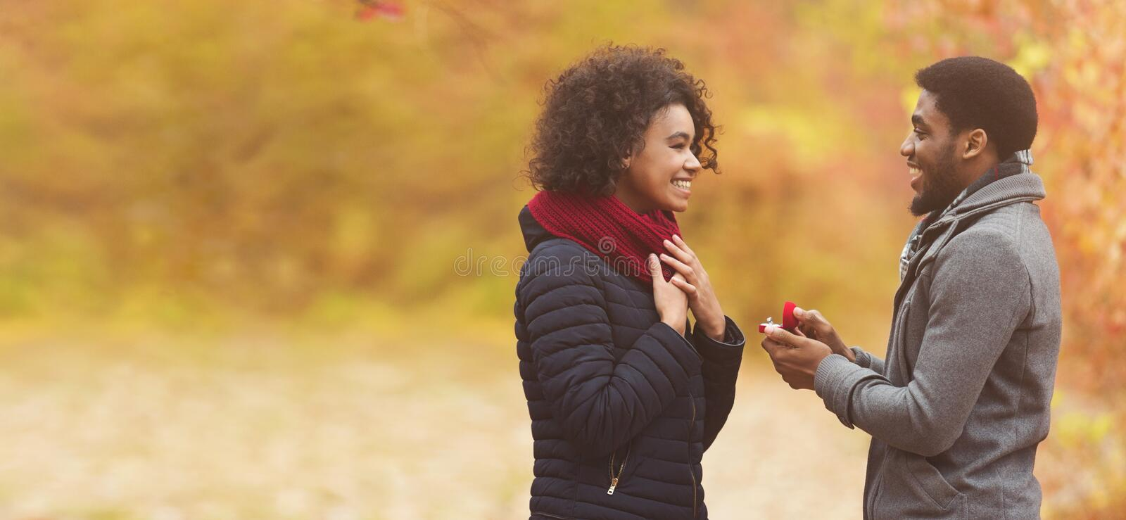 Romantic man proposing to woman in autumn park royalty free stock photos