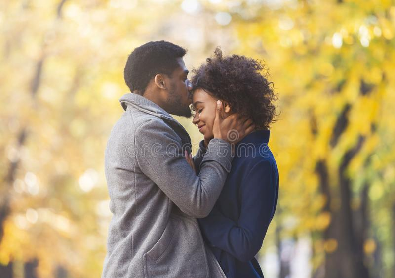 Loving black guy tenderly kissing his woman forehead royalty free stock photo