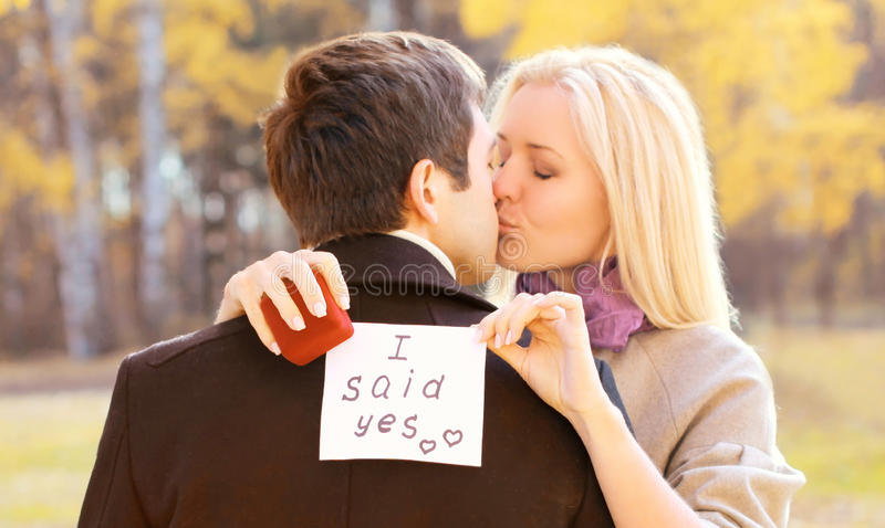 Love, relationships, engagement and wedding concept - man proposes a woman to marry, red box ring, happy romantic couple kissing stock photos