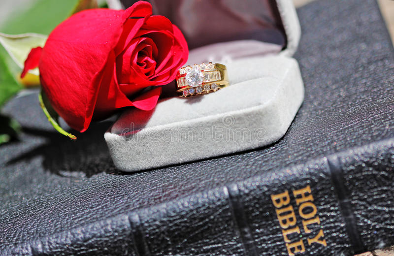 Love and Religion. A red rose, a diamond anniversary ring in an open gray jewelry box on top of a Holy Bible. Concept of Christian renewal of marriage, wedding stock photos